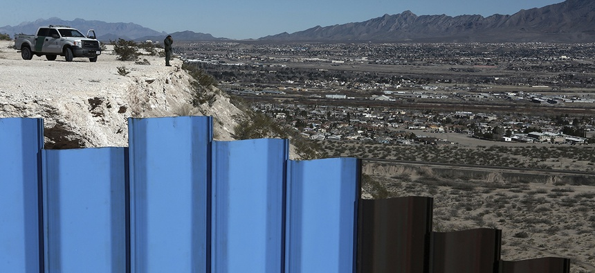 An agent of the border patrol, observes near the Mexico-US border fence, on the Mexican side, separating the towns of Anapra, Mexico and Sunland Park, New Mexico.