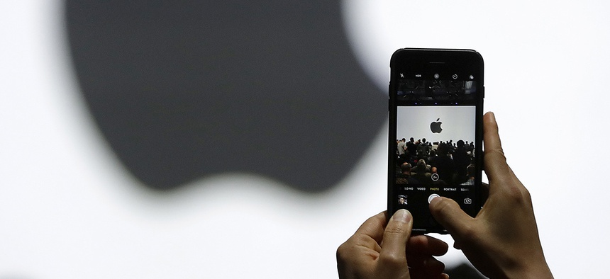 A person takes a photo of an Apple logo before an announcement of new products at the Apple Worldwide Developers Conference on June 5, 2017.