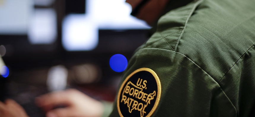 A Border Patrol agent uses a headset and computer to conduct a long distance interview by video from a facility in San Diego.
