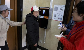 March 21, 2017, visitors to the toilet at the Temple of Heaven park try out a facial recognition toilet paper dispenser in Beijing, China.