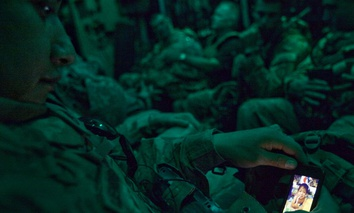 Staff Sgt. Rulberto Qjendismiranda, 20, of Seaside, Calif, with the U.S. Army's 2nd Battalion 27th Infantry Regiment based in Hawaii, looks at a photo of his son Marziano, 11 months, on his mobile phone aboard a military transport flight.