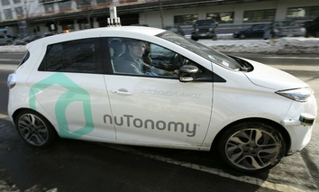An autonomous vehicle is driven by an engineer on a street through an industrial park, in Boston.