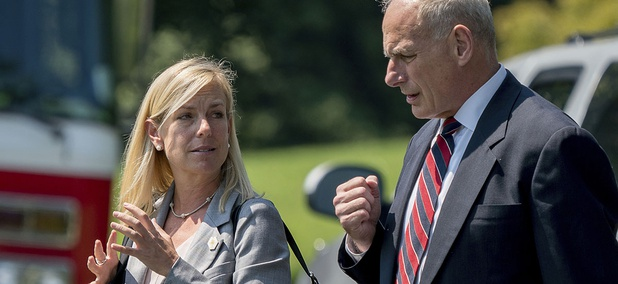 White House Chief of Staff John Kelly and Kirstjen Nielsen speak together as they walk across the South Lawn of the White House in Washington, Tuesday, Aug. 22, 2017