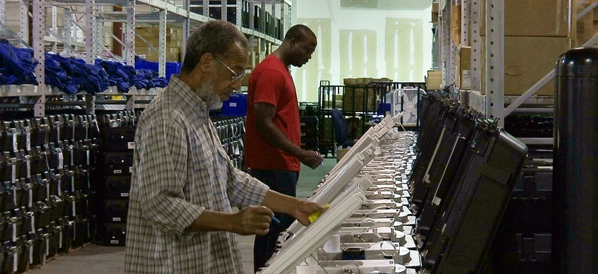 This Sept. 22, 2016 photo shows employees of the Fulton County Election Preparation Center in Atlanta test electronic voting machines.