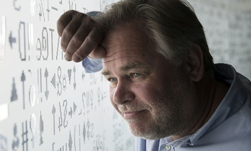 Eugene Kaspersky, Russian antivirus programs developer and chief executive of Russia's Kaspersky Lab, watches trough a window decorated with programming code's symbols at his company's headquarters in Moscow, Russia, Saturday, July 1, 2017.