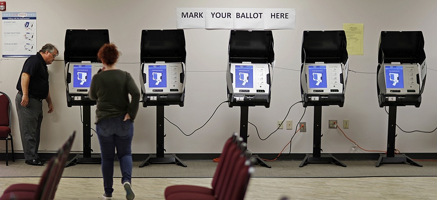 Kelly Monroe, investigator with the Georgia secretary of state office, left, takes a look at a new voting machine being tested at a polling site in Conyers, Ga.