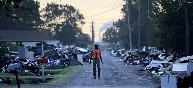 A man walks past debris from homes on his street damaged in flooding from Hurricane Harvey as an oil refinery stands in the background in Port Arthur, Texas, Thursday, Sept. 28, 2017.