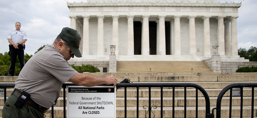 A US Park Police officer watches at left as a National Park Service employee posts a sign on a barricade closing access to the Lincoln Memorial in Washington, Tuesday, Oct. 1, 2013.