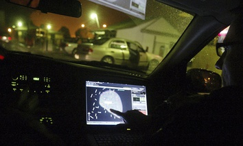 A person points at a GPS inside a vehicle on a residential street. An engineer alerts police of a gunshot detected with a ShotSpotter system in East Palo Alto, California.