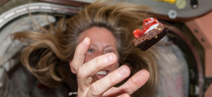 NASA astronaut Karen Nyberg floats a piece of food during mealtime. NASA astronaut Karen Nyberg floats a piece of food during mealtime.