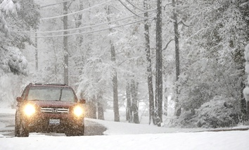 A vehicle drives along Lakeway Drive as snow covers the area following an early morning snowstorm, Friday, Dec. 8, 2017, in Brandon, Miss.