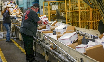 Steve Robino arranges packages on a conveyor belt at the main post office in Omaha, Neb., Thursday, Dec. 14, 2017.