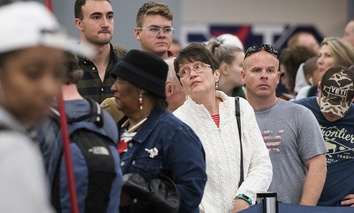 People wait in line to rebook flights at Hartfield-Jackson Atlanta International Airport , Monday, Dec. 18, 2017.