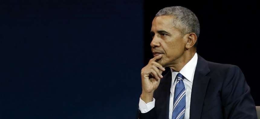 Former President Barack Obama pauses as he gives a speech in Paris, Dec. 2.