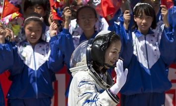 Chinese students wave flowers and national flags as female astronaut Wang Yaping leaves the Jiuquan satellite launch center for the launch site, near Jiuquan in western China's Gansu province, Tuesday, June 11, 2013.
