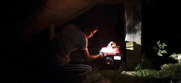 resident Karina Santiago Gonzalez works on a small power plant in Morovis, Puerto Rico.