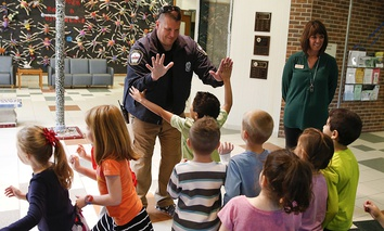 Forest Dale Elementary School principal Deanna Pitman, right, and Carmel, (Ind.) police officer Greg DeWald welcome students as they return to the school following an intruder drill at the school in Carmel, Ind.