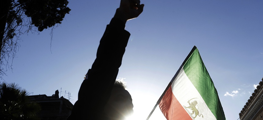 A demonstrator shouts slogans near the flag of the former Imperial State of Iran as he gathers with supporters of Maryam Rajavi, head of the Iranian opposition group National Council of Resistance, outside the Iran Embassy, in Rome, Tuesday, Jan. 2, 2018.