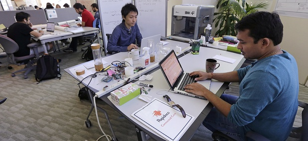 Babson College graduate school alumnus and Visa applicant Abhinav Sureka, of Mumbai, India, right, types in his work space at the college in Wellesley, Mass.