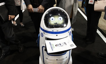 Evolver's Fabo E01 service robot carries flyers at CES International, Wednesday, Jan. 10, 2018, in Las Vegas.