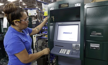 Employee Maria Edney installs software onto an automated teller machine during the manufacturing process at Diebold Nixdorf in Greensboro, N.C.