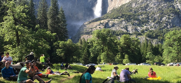 Visitors sit in a meadow at Yosemite National Park, Calif., below Yosemite Falls.