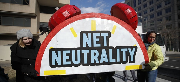 """Protesters carry the top of an alarm clock display that reads """"Net Neutrality"""" after a protest at the FCC headquarters in Washington."""