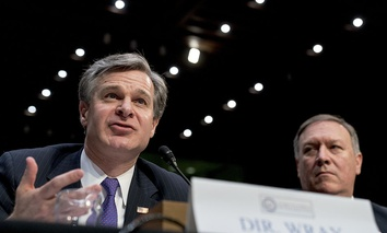 FBI Director Christopher Wray, accompanied by CIA Director Mike Pompeo, right, speaks at a Senate Select Committee on Intelligence hearing on worldwide threats, Tuesday, Feb. 13, 2018.
