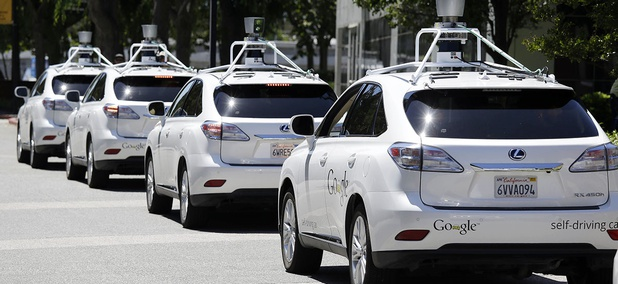A row of Google self-driving Lexus cars at a Google event outside the Computer History Museum in Mountain View, Calif.