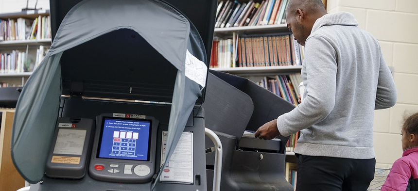 A voter casts his ballot into an electronic voting machine at a polling station in Cincinnati. Ohio.