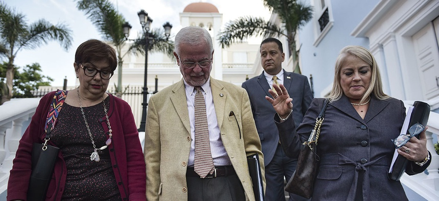 Puerto Rico secretary of the Department of Public Security, Hector Pesquera, center, Puerto Rico Justice Secretary Wanda Vazquez, right, and U.S. Attorney Rosa Emilia Rodriguez, head to give a press conference in San Juan, Puerto Rico.