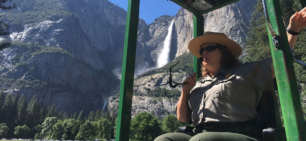 A guide at Yosemite National Park, Calif., talks to tourists with Yosemite Falls behind her.