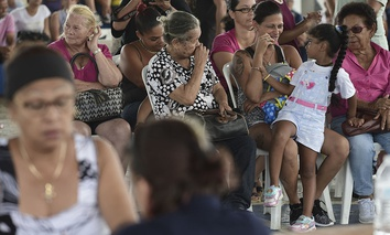 People wait at the Jose de Diego Elementary School to file FEMA forms for federal aid in the aftermath of Hurricane Maria in Las Piedras, Puerto Rico, Monday, Oct. 2, 2017.