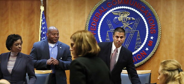Federal Communications Commission Chairman Ajit Pai, right, and Commissioner Mignon Clyburn, far left, on Dec. 14 in Washington, D.C.