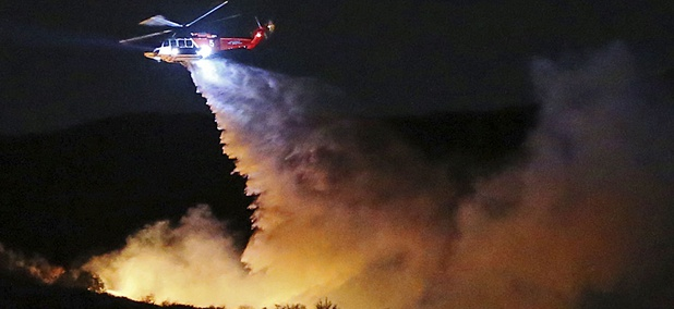 A helicopter makes a water drop on a brush fire that broke out near Los Angeles on Wednesday evening, Feb. 21, 2018.