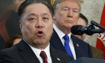 Broadcom CEO Hock Tan speaks while U.S. President Donald Trump listens, in background, during an event at the White House in Washington.