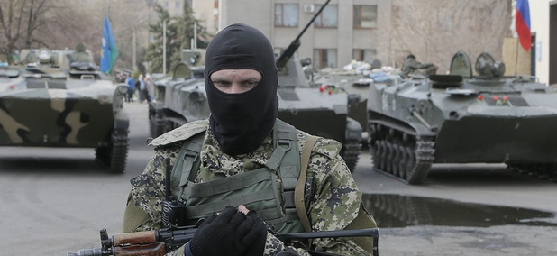 A masked gunman guards combat vehicles with Russian, Donetsk Republic and Ukrainian paratroopers, flags and gunmen on top, parked in downtown of Slovyansk.