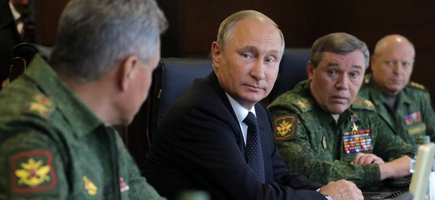 Russian President Vladimir Putin, center, speaks to Defence Minister Sergei Shoigu, left, as Chief of the General Staff of the Russian Armed Forces Valery Gerasimov, second right, looks on.