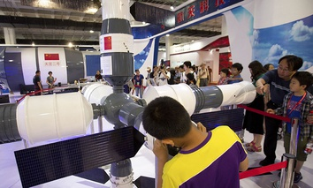 Visitors look at a model of China's Tiangong-1 space station at the China Beijing International High-Tech Expo in Beijing, Saturday, June 10, 2017.