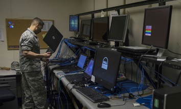 An airman prepares to image a laptop at Yokota Air Base, Japan.
