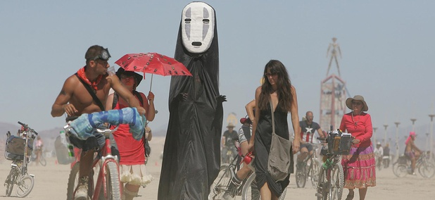 Burning Man participants walk on the playa at the Black Rock Desert near Gerlach, Nev.