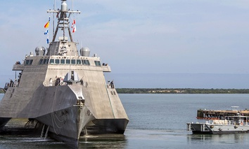 A Naval Station vessel, right, prepares to assist the future USS Omaha (LCS 12), a 218-foot-long littoral combat ship, pier side during a brief fuel stop in Guantanamo Bay, Cuba.