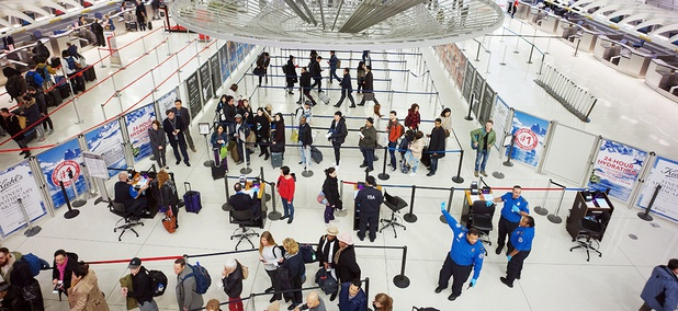 Passengers stand in line as they wait to pass through a TSA security checkpoint at JFK International Airport in New York.