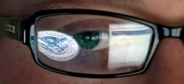 A reflection of the Department of Homeland Security logo is seen reflected in the glasses of a cyber security analyst in the watch and warning center at the Department of Homeland Security's secretive cyber defense facility at Idaho National Laboratory.