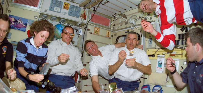 The crew of shuttle mission STS-110 eats dinner