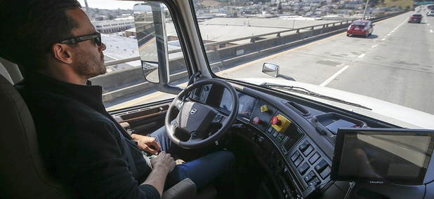 Matt Grigsby, senior program engineer at Otto, takes his hands off the steering wheel of a self-driving, big-rig truck during a demonstration on the highway, in San Francisco.