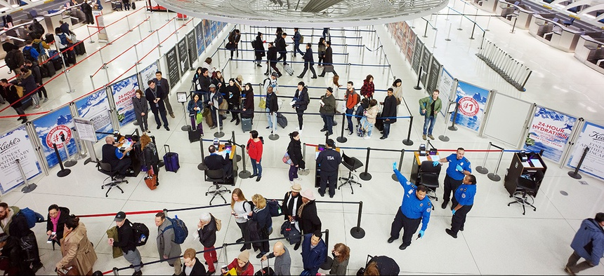 Passengers stand in line as they wait to pass through a TSA security checkpoint at JFK International Airport Friday, March 2, 2018.