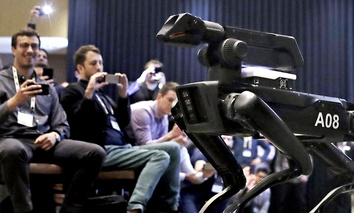A Boston Dynamics SpotMini robot is walks through a conference room during a robotics summit in Boston.