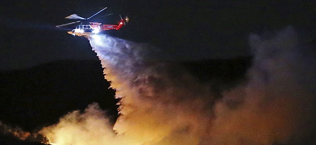 a helicopter drops water on a brush fire that broke out in Topanga State Park, Los Angeles.