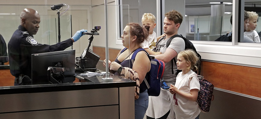 A customs agent, left, adjusts a face recognition camera as he screens a family after their recent international flight arrival at Orlando International Airport, Thursday, June 21, 2018.